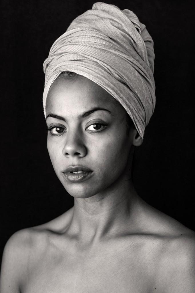 Portrait von Larissa, Anfang/Mitte Zwanzig. Sie ist Halbafrikanerin und trägt einen Turban aus gewickeltem Tuch.