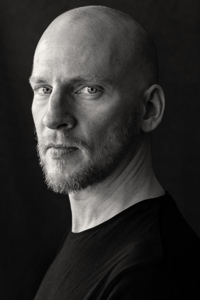 Ein Mann um die 40, fotografiert von Astrid Schulz. Er trägt einen Bart und eine Glatze. Sein Blick ist stolz. Schwarz-Weiss-Portrait.