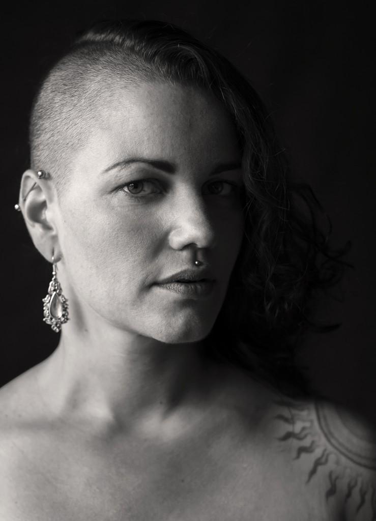 Die Fotografin Astrid Schulz portraitierte eine Frau um die 30. Sie trägt einen Sidecut. Ihre Ohren sind gepierct und sie trägt ein Medusa-Piercing.
