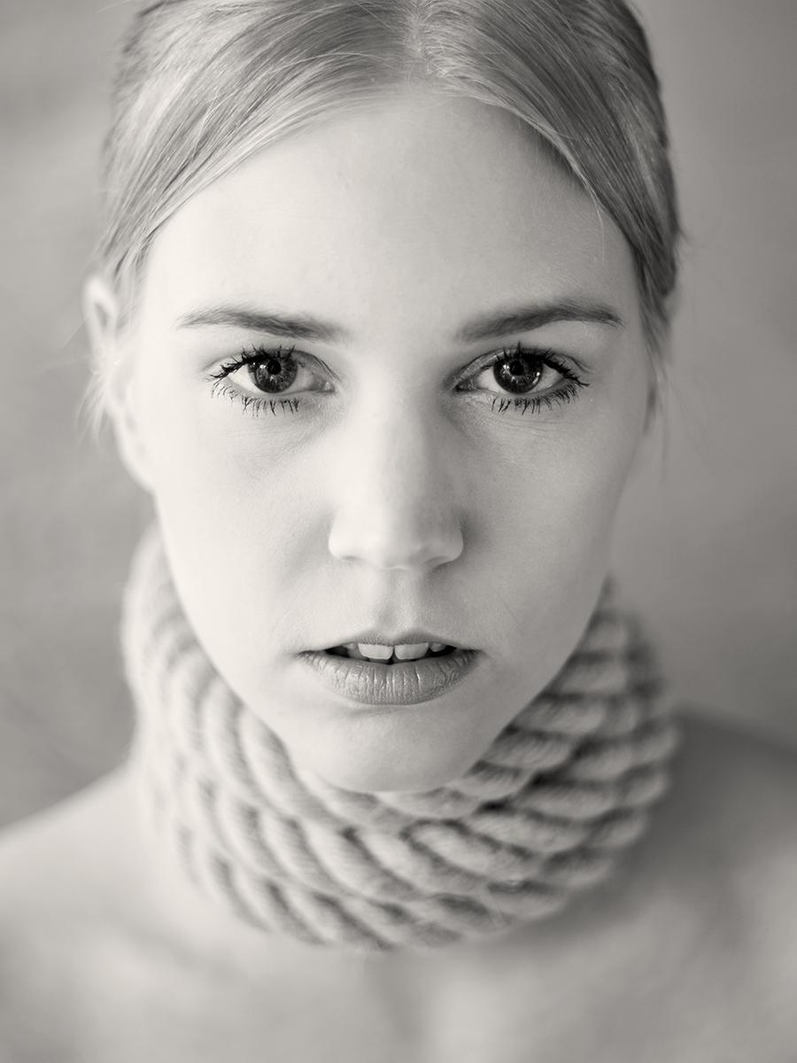 Fotografin Astrid Schulz hat das Modell Corinna portraitiert. Die junge blonde Frau hat die Haare streng zurückgebunden. Ihren Hals schmückt ein dickes Seil, es ist eng um ihren Hals gebunden. Ihr Blick geht direkt in die Kamera.