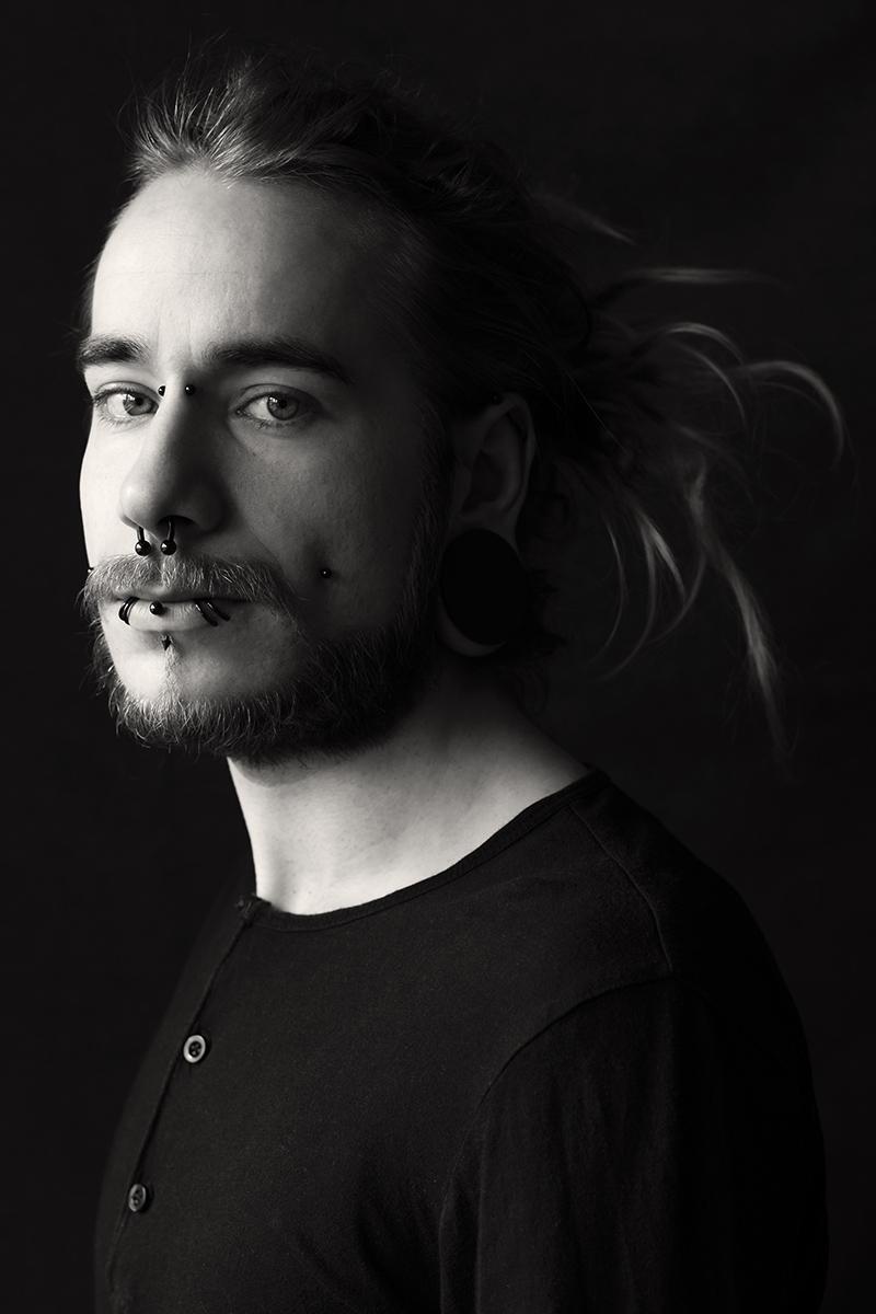 Portrait von Sebastian vor dunklem Hintergrund. Er hat einige Piercings im Gesicht.