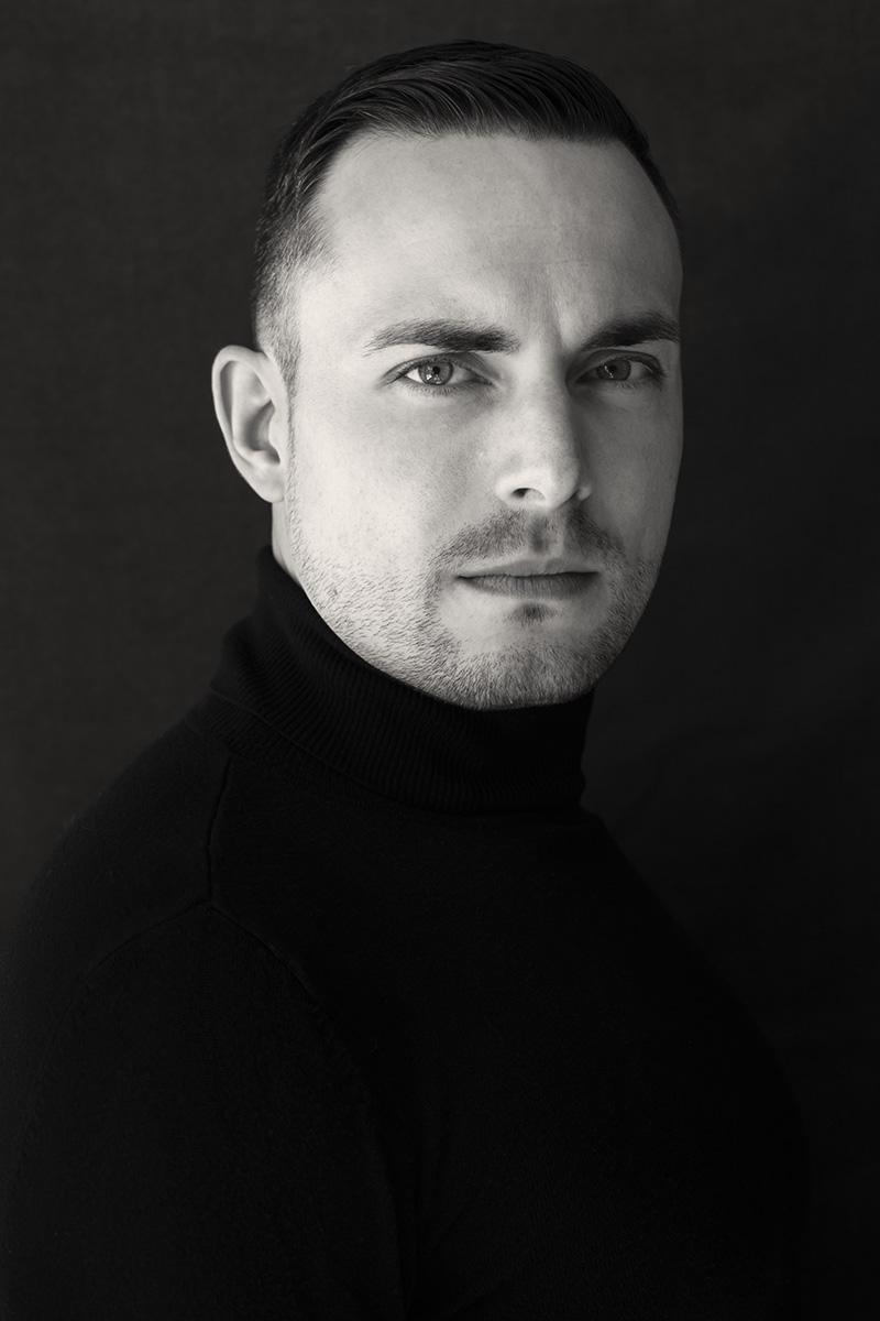 Portrait eines Mannes, der einen schwarzen Rollkragenpullover trägt.