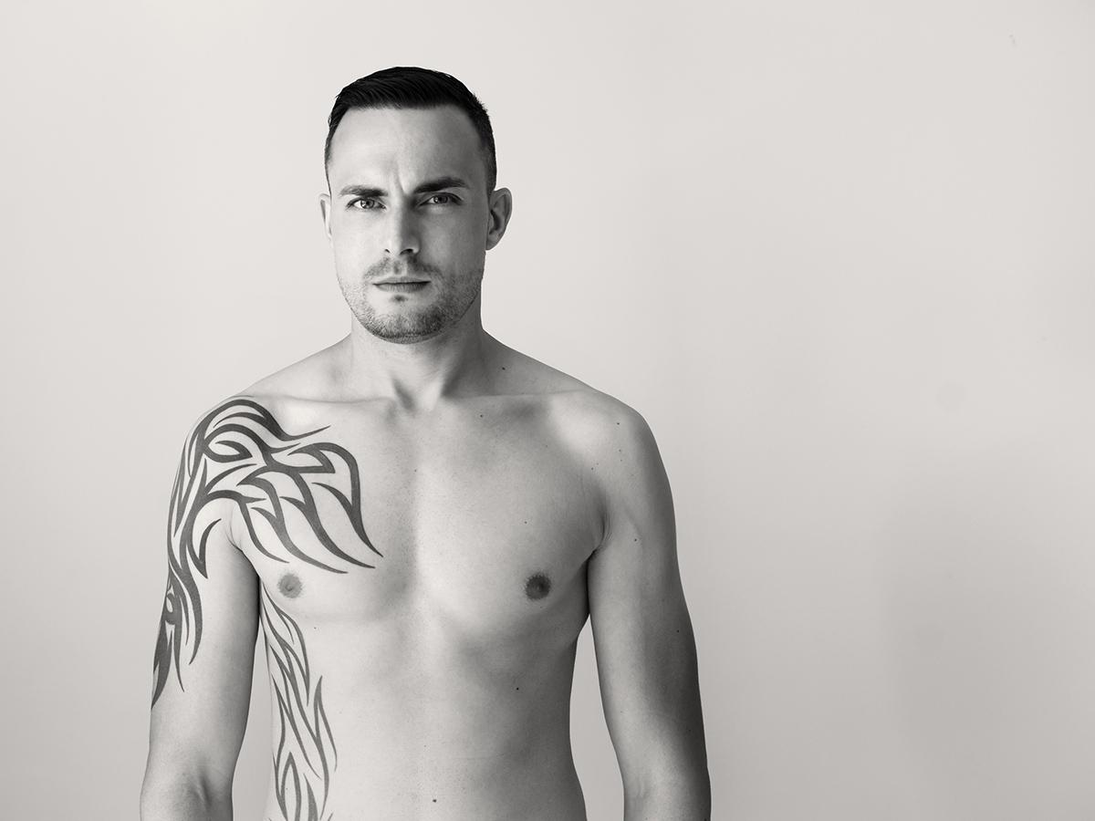 Ein Mann um die 30 steht vor einem weißen Hintergrund. Er hat kein Oberteil an. Seine rechte Körperhälfte ist tätowiert.