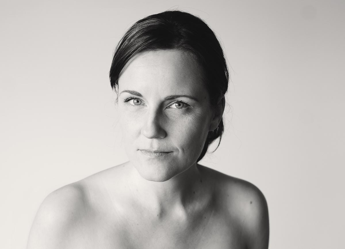 Portrait einer dunkelhaarigen Frau vor hellem Hintergrund. Fotografin: Astrid Schulz aus Bremen. Schwarz-weiß-Fotografie vom feinsten.