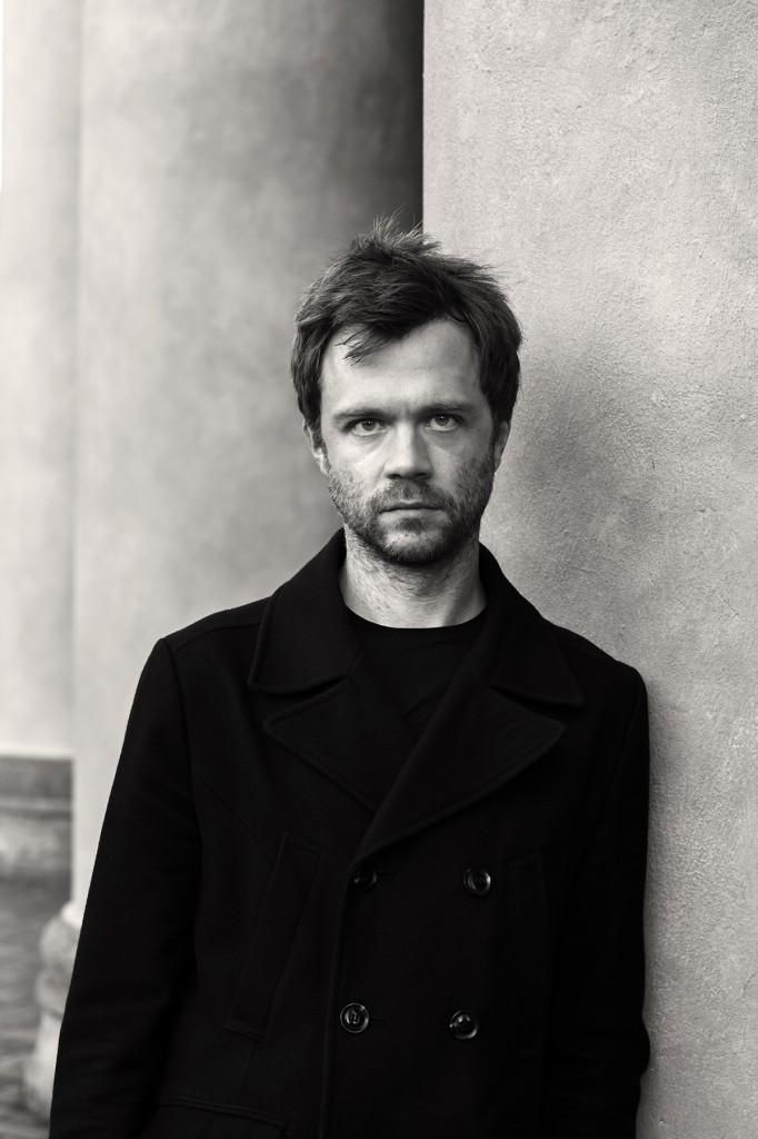 Ein Mann im schwarzen Mantel und drei-Tage-Bart lehnt an einer Säule und schaut in die Kamera. Schwarz-Weiß-Foto.