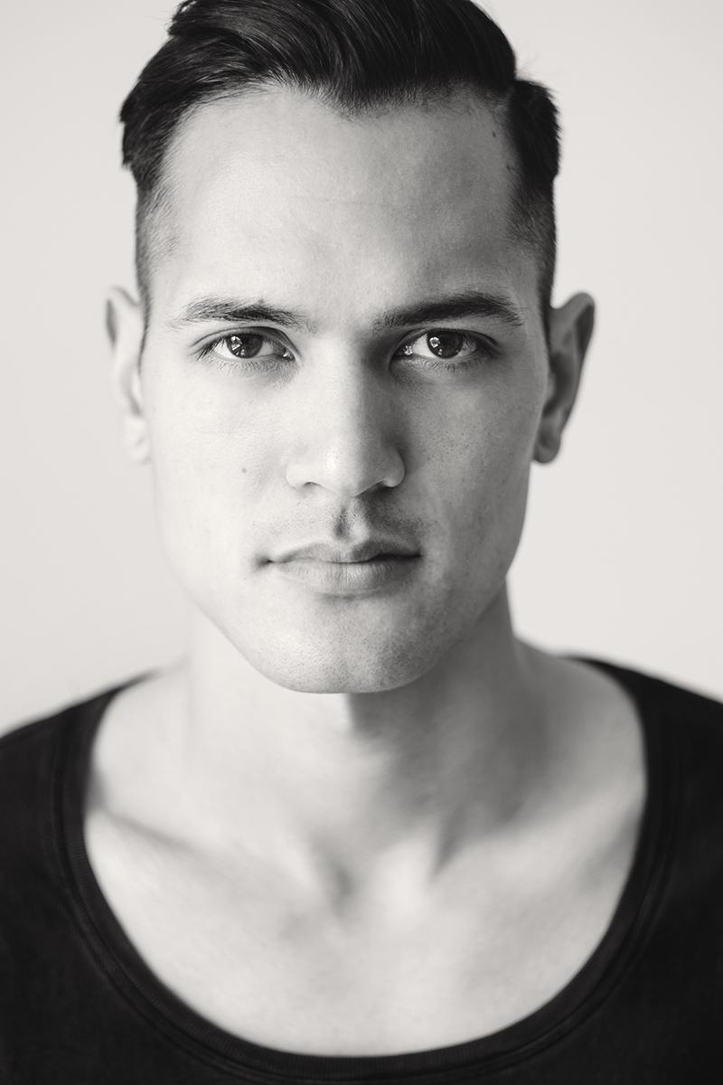 Schwarz-weiß-Portrait eines jungen Mannes mit asiatischen Gesichtszügen.