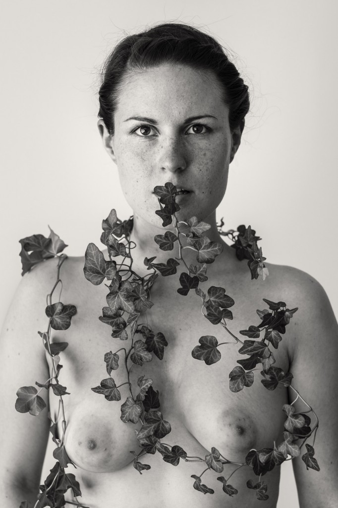 Aktportrait einer dunkelhaarigen, sommersprossigen Frau. Um ihren Oberkörper rankt Efeu. Fotografiert von Astrid Schulz aus Bremen