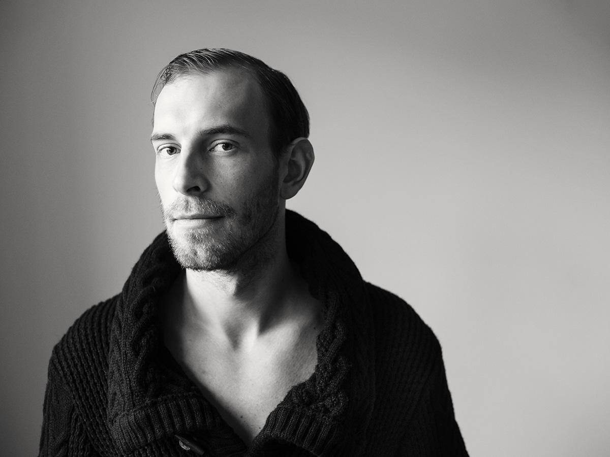 Schwarz-weiß-Portrait eines jungen Mannes. Er trägt einen dicke, dunkle Strickjacke und guckt ernst in die Kamera. Charakterportrait von Fotografin Astrid Schulz aus Bremen.