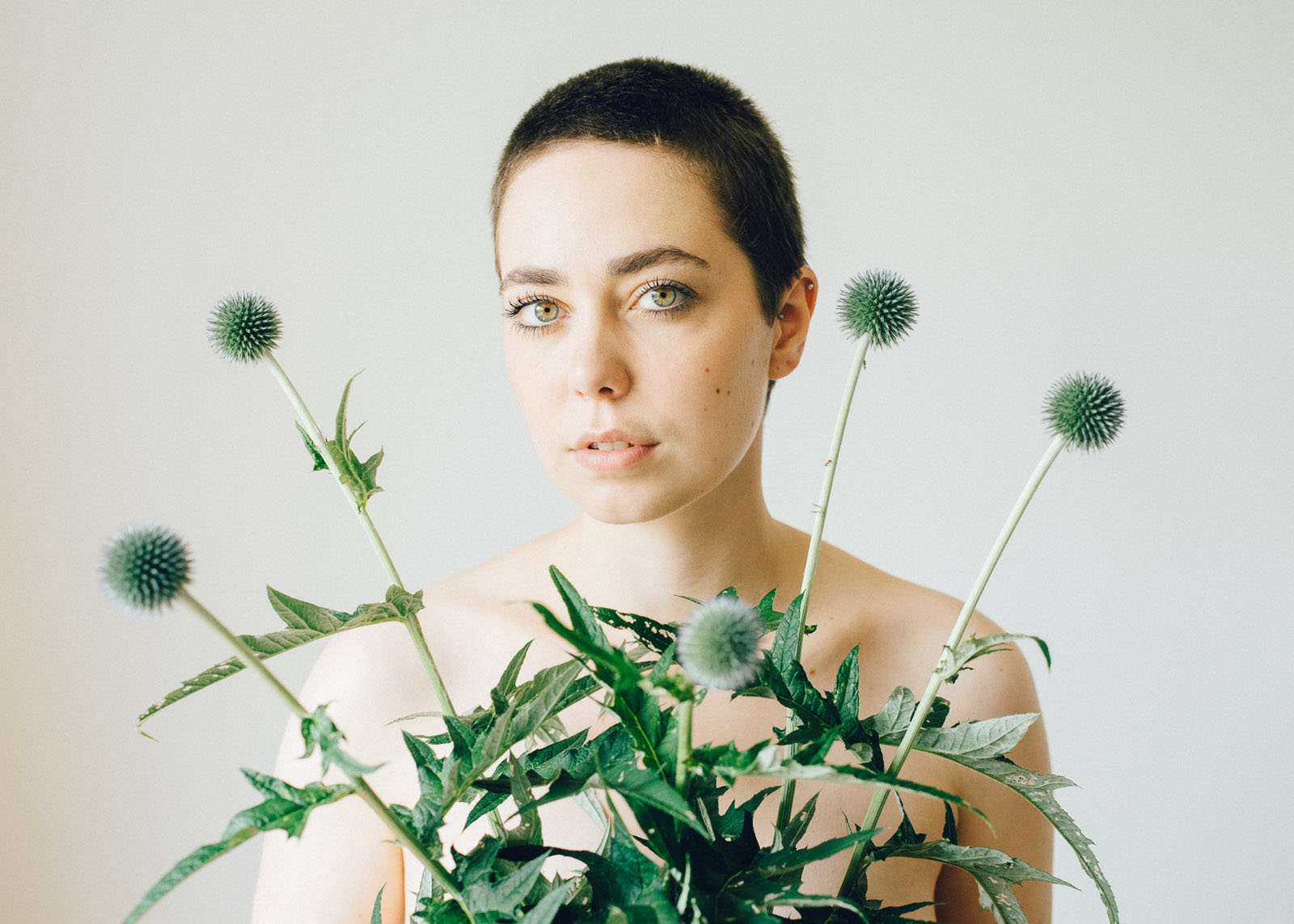 Portrait einer Frau namens Liv, sie trägt fünf Disteln vor sich.