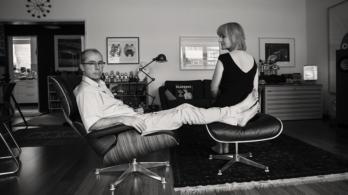 Man sieht ein Paar in seiner Wohnung. Er sitzt auf einem Sessel, davor ein Hocker, auf dem seine Füße liegen. Auf dem Hocker sitzt auch seine Partnerin. Sie ist mit dem Rücken zu uns gewandt und blickt zur Seite auf ihren Mann.
