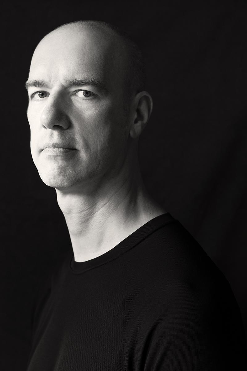 Porträt von Stefan vor einem dunklen Hintergrund.