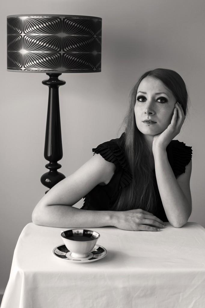 Eine junge Frau sitzt an einem Tisch. Vor ihr steht eine Tasse Tee. Sie hat ihren Kopf auf ihre linke Hand gestützt und blickt in die Kamera. Fotografiert von Astrid Schulz aus Bremen.