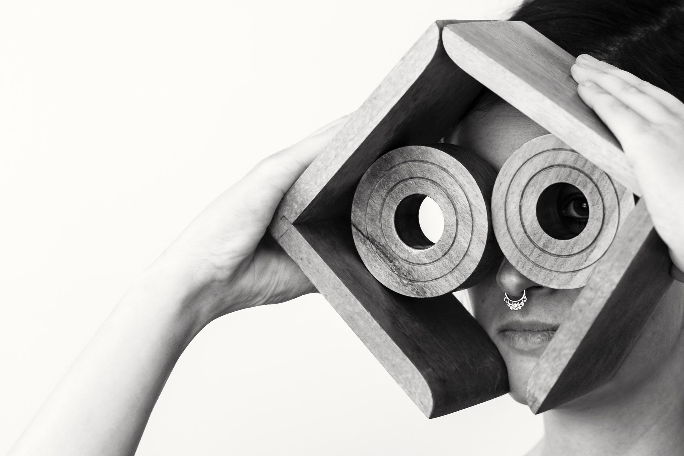 """Eine Frau hält Buchstützen aus Holz vor ihr Gesicht. Durch die """"Gucklöcher"""" der runden Holzstücke schaut sie in die Ferne. Schwarz-weiß-Fotografie von Fotografin Astrid Schulz, Bremen."""