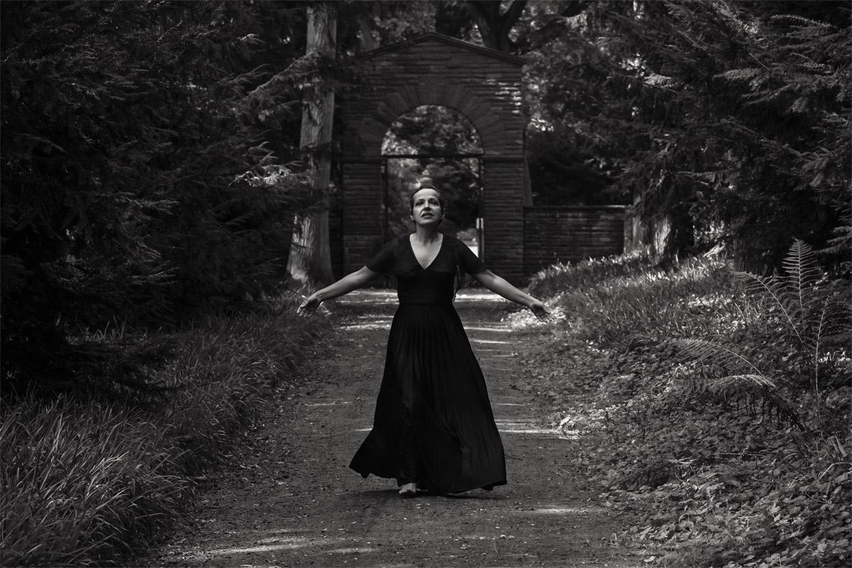 Ein Foto im Park: Eine Frau im langen schwarzen Abendkleid rennt mit weit offenen Armen dem Fotograf entgegen. Aufgenommen von Fotografin und Künstlerin Astrid Schulz aus Bremen.