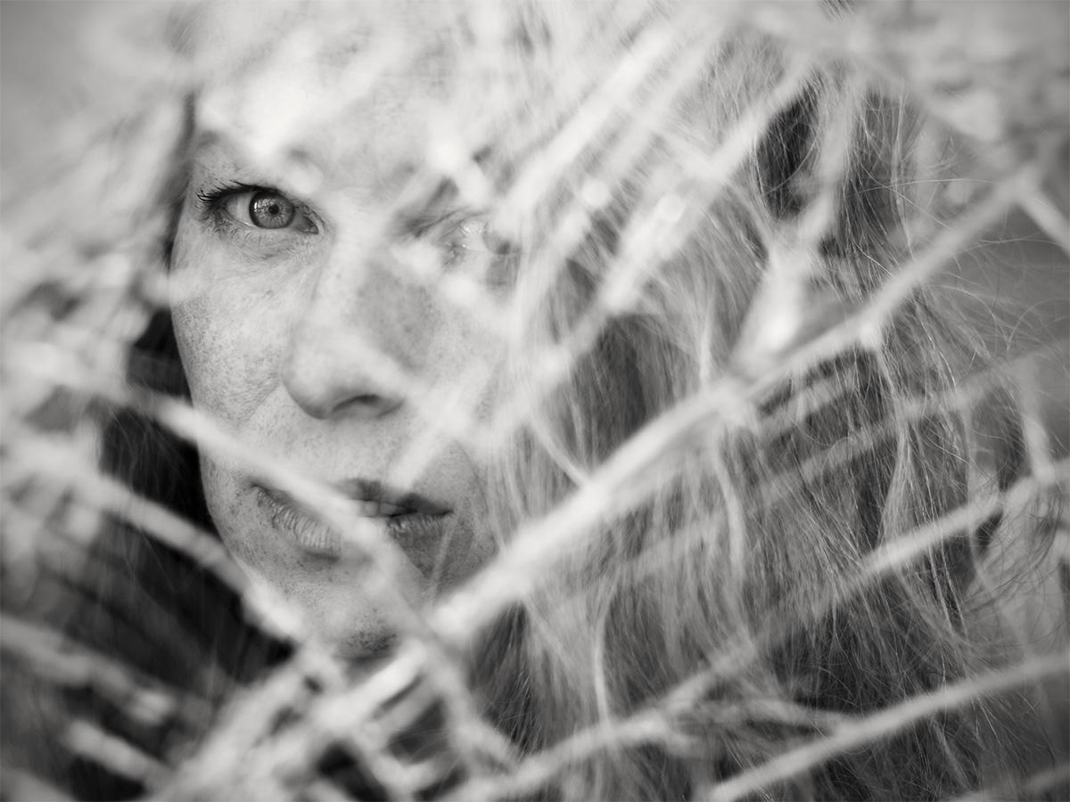Portrait von Elke durch eine zersplitterte Glasscheibe. Schwarz-Weiß-Foto.