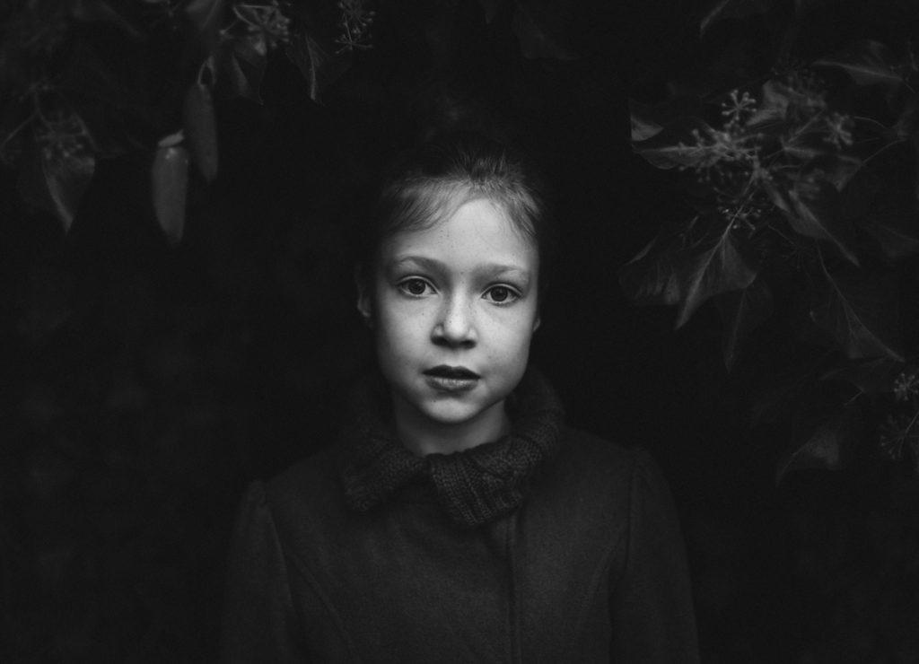 Fotografin Astrid Schulz porträtierte eine Siebenjährige. Das Mädchen steht vor einer Efeuwand und blickt in die Kamera.