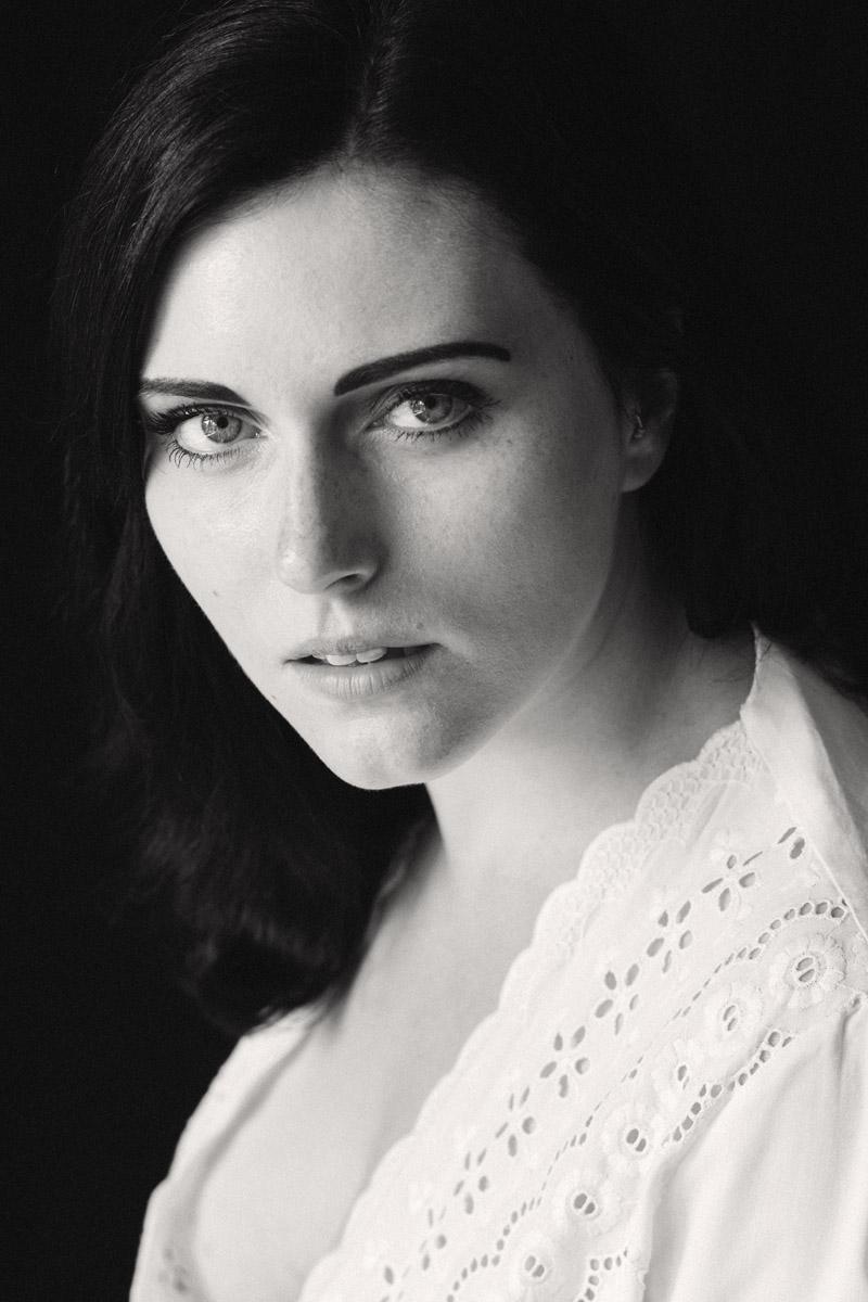Portrait einer jungen, dunkelhaarigen Frau mit ausdrucksvollen Augen.