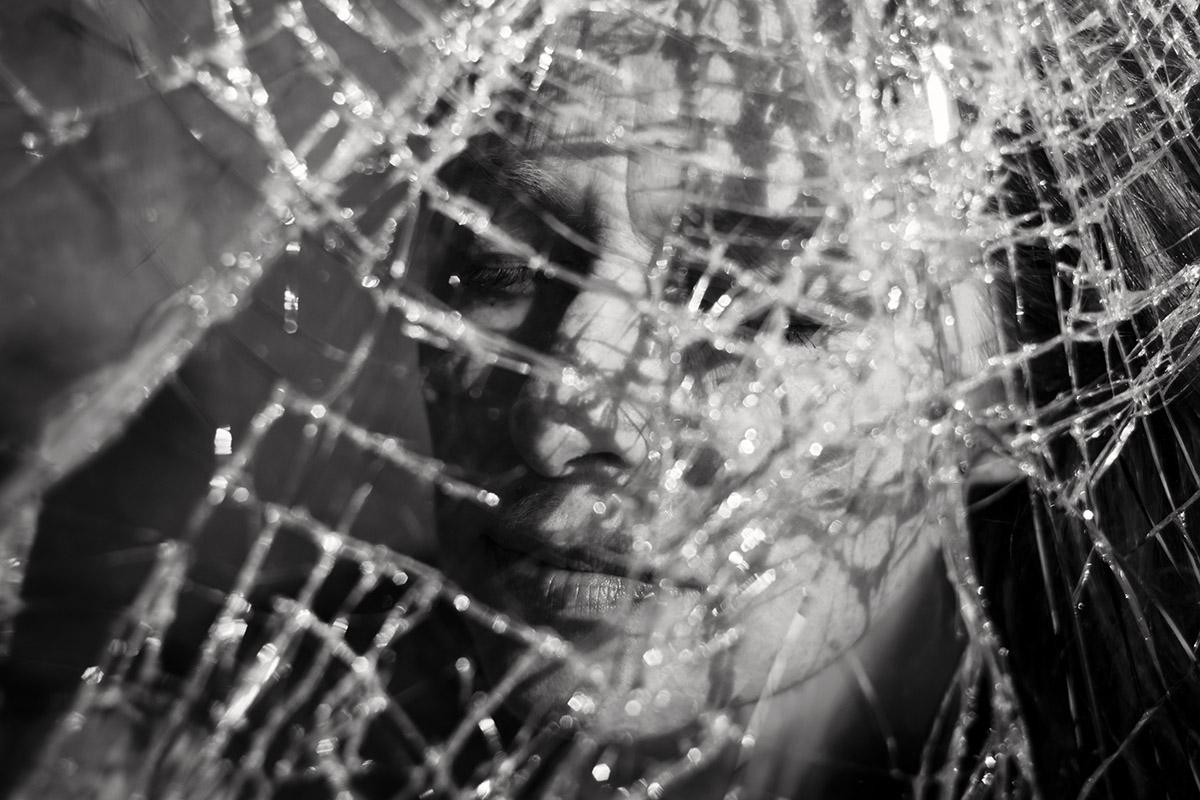 Fotografin Astrid Schulz fotografierte eine Frau durch eine zerbrochene Fensterscheibe. Die Frau hat die Augen geschlossen. Die Sonne scheint durch die zerbrochene Scheibe und wirft die Schatten der Risse auf ihr Gesicht.