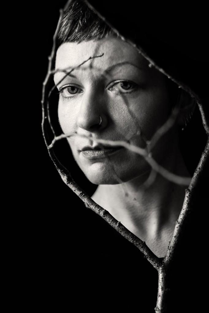 Sie sehen ein schwarz-weiß-Porträt einer Frau, die hinter Ästen hervorblickt, direkt in die Kamera. Die Äste umrahmen ihr Gesicht und laufen auch in ihr Gesicht hinein. Die Äste umrahmen ihr Gesicht, an den Außenkanten ist alles schwarz. Aufgenommen von Astrid Schulz, Fotografin aus Bremen.