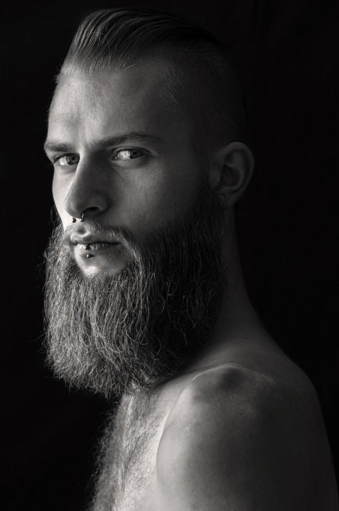 Schwarz-weiß-Portrait von Marcus. Er trägt einen langen Bart und Piercings.