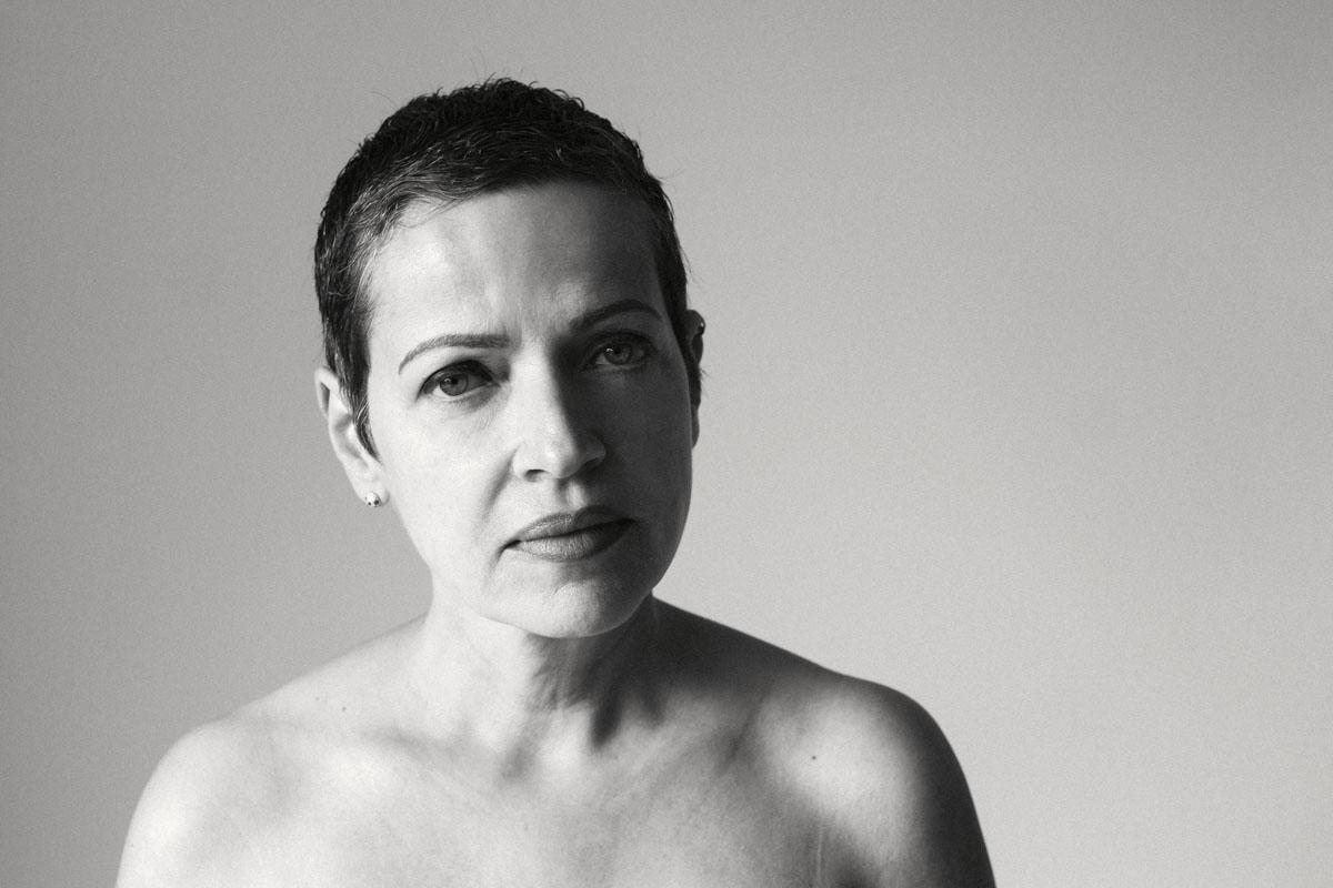 Mirjam, 54, wurde von Astrid Schulz portraitiert. Die Frau trägt einen sehr kurzen Haarschnitt. Es ist ein schwarz-weiss Foto