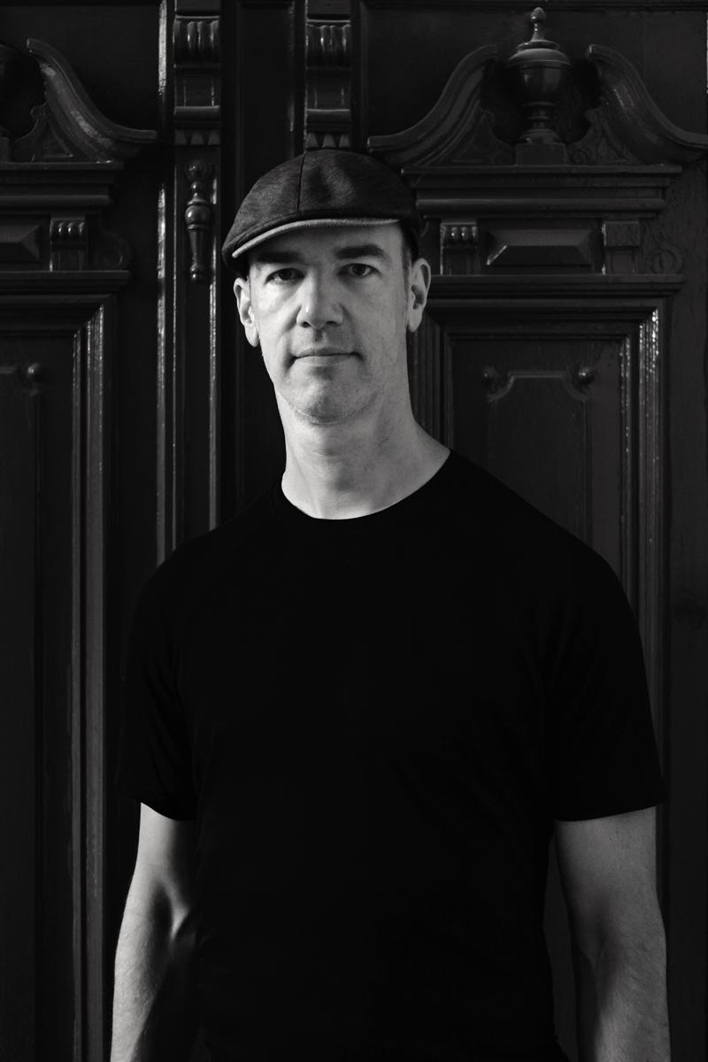 """Schwarz-Weiß-Portrait eines Mannes. Er trägt eine Kappe und sieht """"very british"""" aus."""