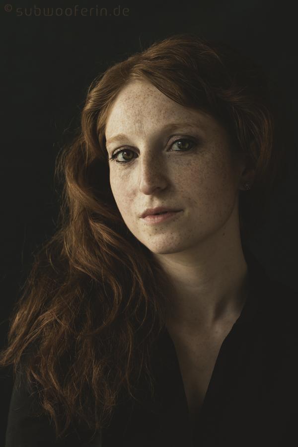 Portrait einer rothaarigen Frau mit Sommersprossen. Es erinnert an ein Gemälde alter Meister. Aufgenommen von Fotografin Astrid Schulz aus Bremen.