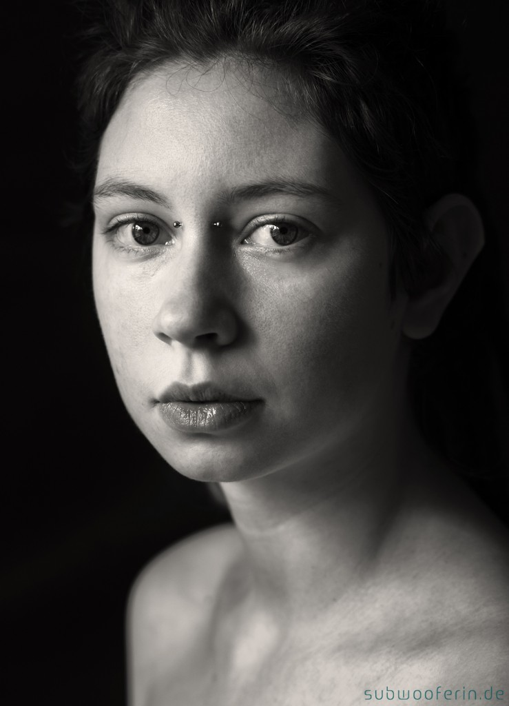 Eine junge Frau schaut in die Kamera. Schwarz-weiß-Porträt von Astrid Schulz, Fotografin aus Bremen.