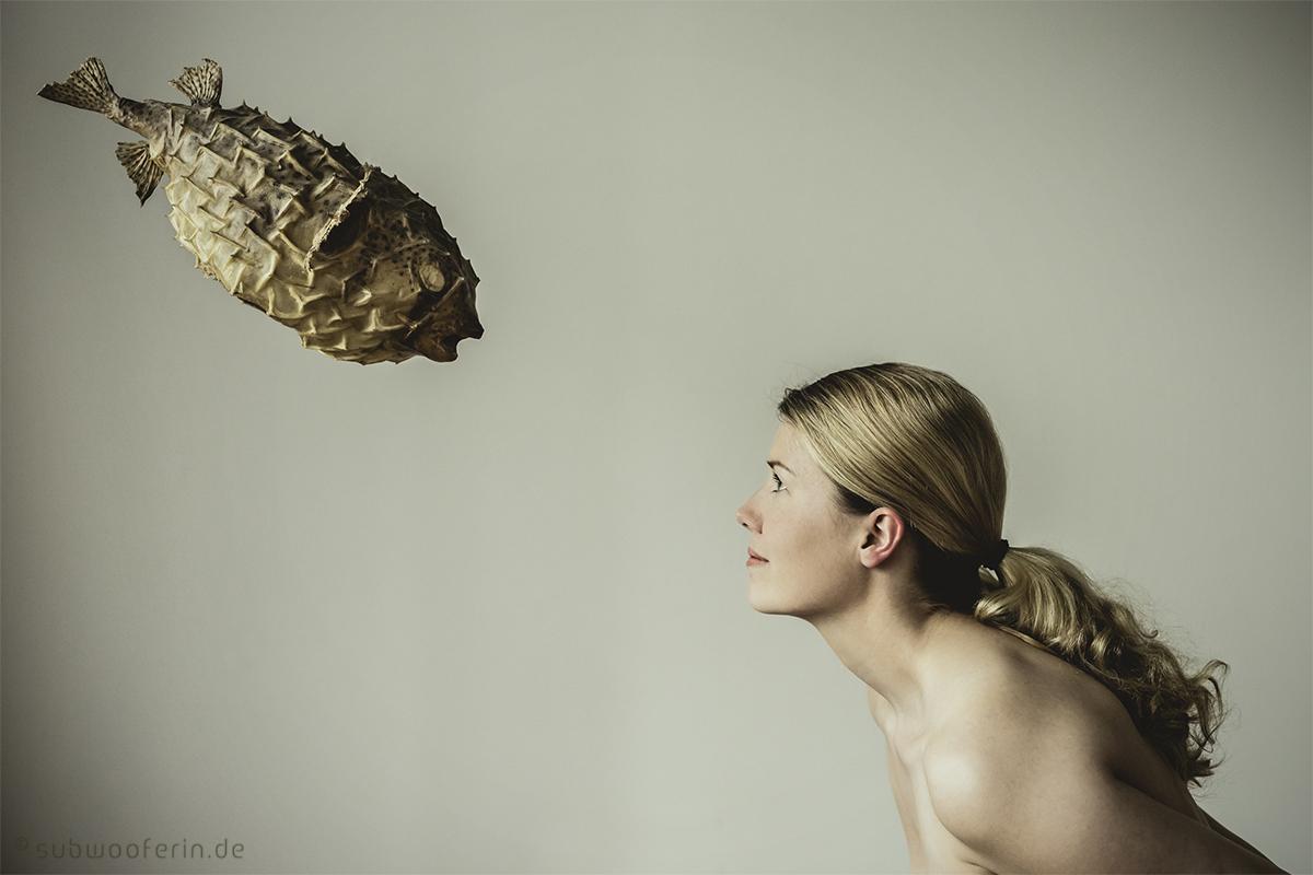 Eine surreale Szene: Kugelfisch schaut einer blonden Frau direkt in die Augen. Seitenansicht. Fotografin Astrid Schulz aus Bremen. Kein Composing.