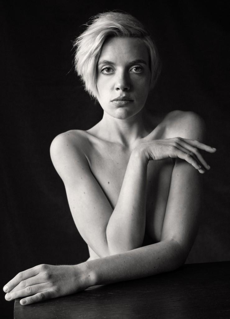 Verdeckter Akt: Eine blonde Frau sitzt an einem Tisch. Sie hat große Augen und Ähnlichkeit mit Twiggy.